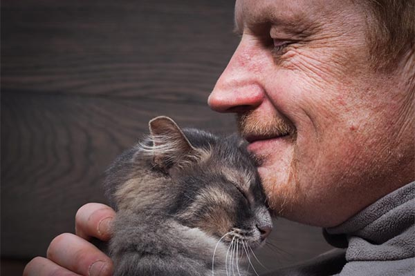Man with his face pressed against a cats forehead